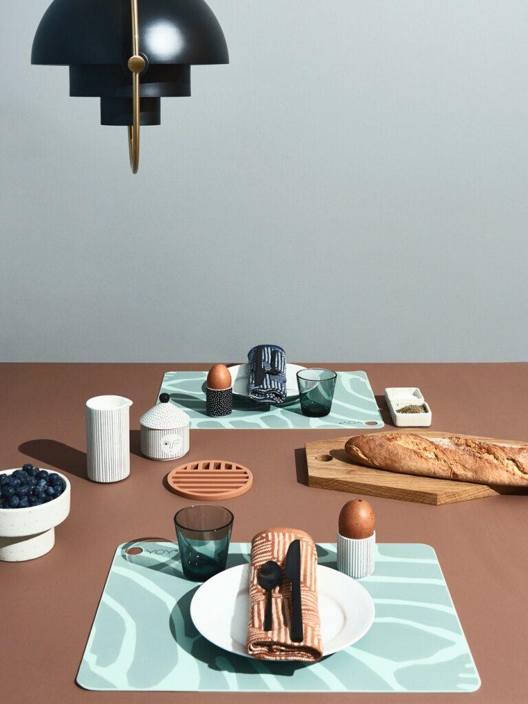 שולחן עם מפה חומה, פלייסמנטים בגוון תכלת עם דוגמת גלים