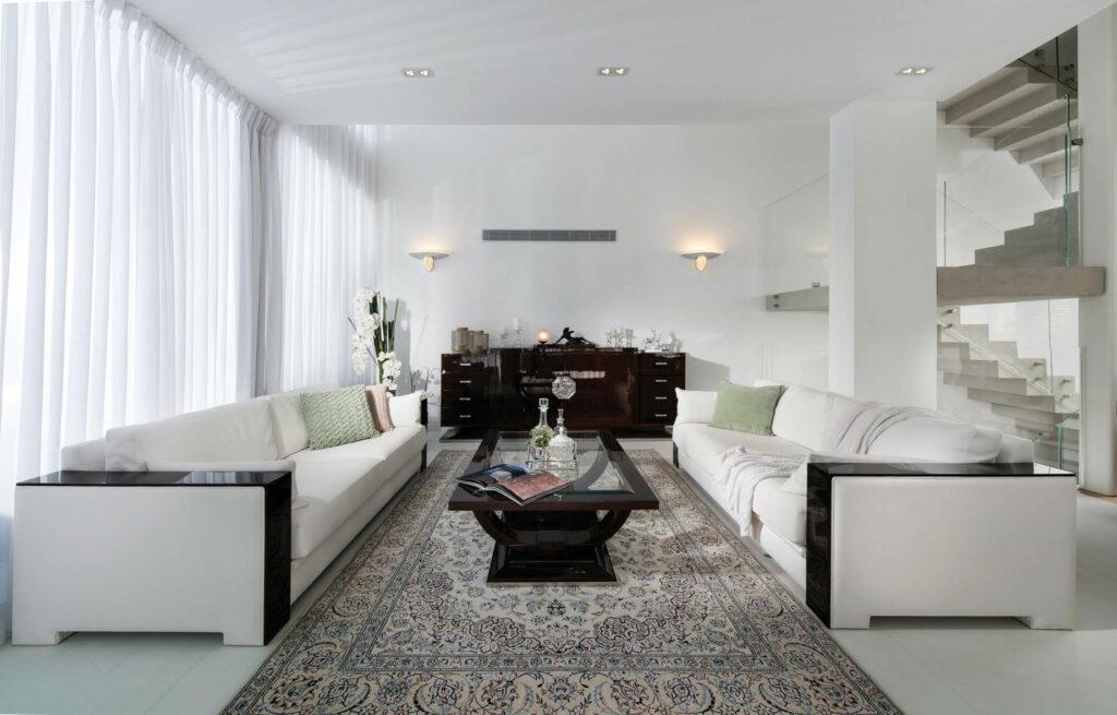חלל המגורים בצבעוניות מונוכרומטית של קירות לבנים, רצפה בהירה וטקסטילים תואמים