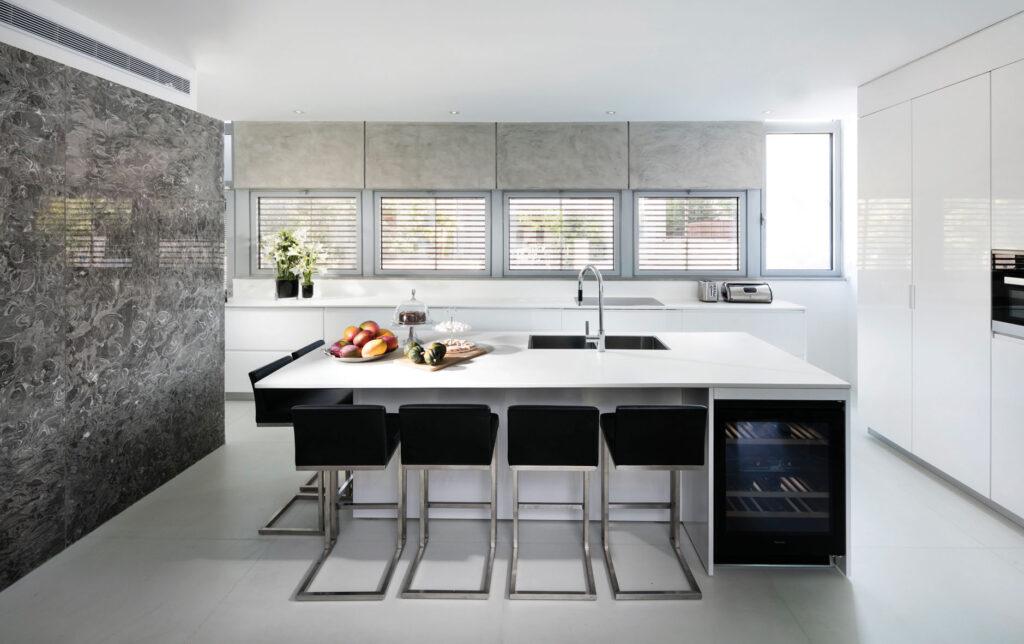 המטבח: ארונות תחתונים לבנים, חלונות הפונים אל הגינה ואי עבודה גדול המשמש גם כשולחן אוכל