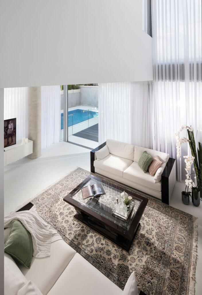 מבט מהקומה השנייה אל חלל המגורים והבריכה