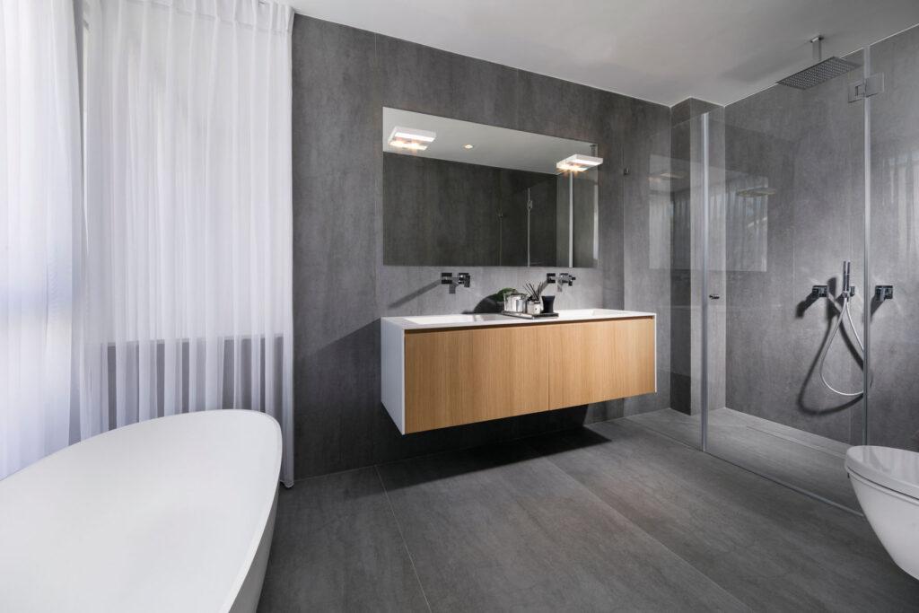 חדר אמבטיה גדול הכולל מקלחת זוגית, יחידת ארונית זוגית ואמבטיית פרי-סטנדינג המשקיפה אל הבריכה