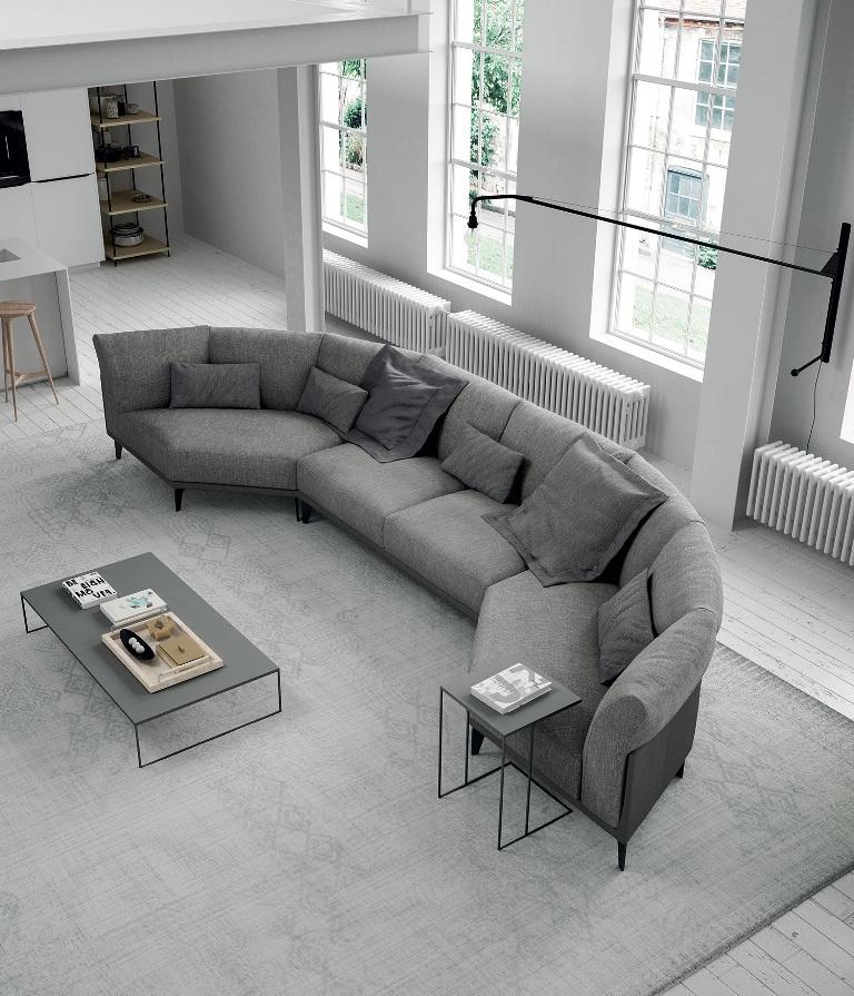 ספה בצורת חצי מעגל, מרופדת באריג אפור, וכריות בגוונים שונים של אפור, בעיצוב Doimo Salotti
