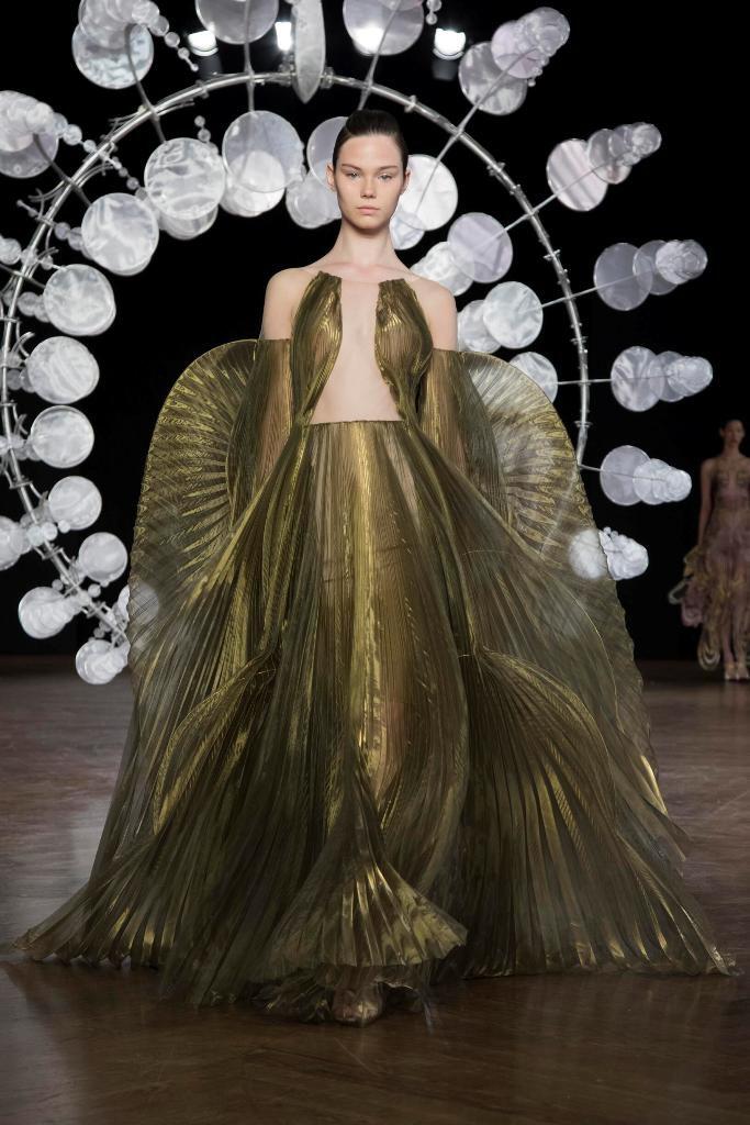 שמלת פליסה מוזהבת במראה פיסולי בשילוב גלימה שמתחילה בזרוכות הידיים, בעיצוב איריס ואן-הרפן