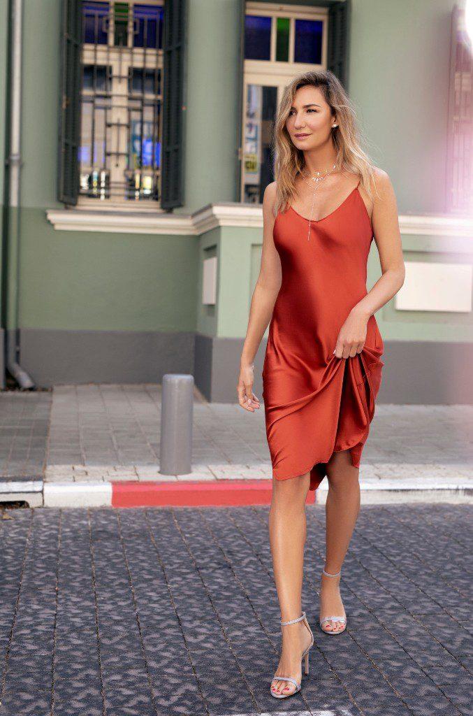 מיכל אנסקי מציגה נעליים מתוך קולקציית מיכאלה בעיצובה בשיתוף עם רשת לאפייט. בתמונה סנדלי ערב כסופים שמותאמים לשמלה אדומה