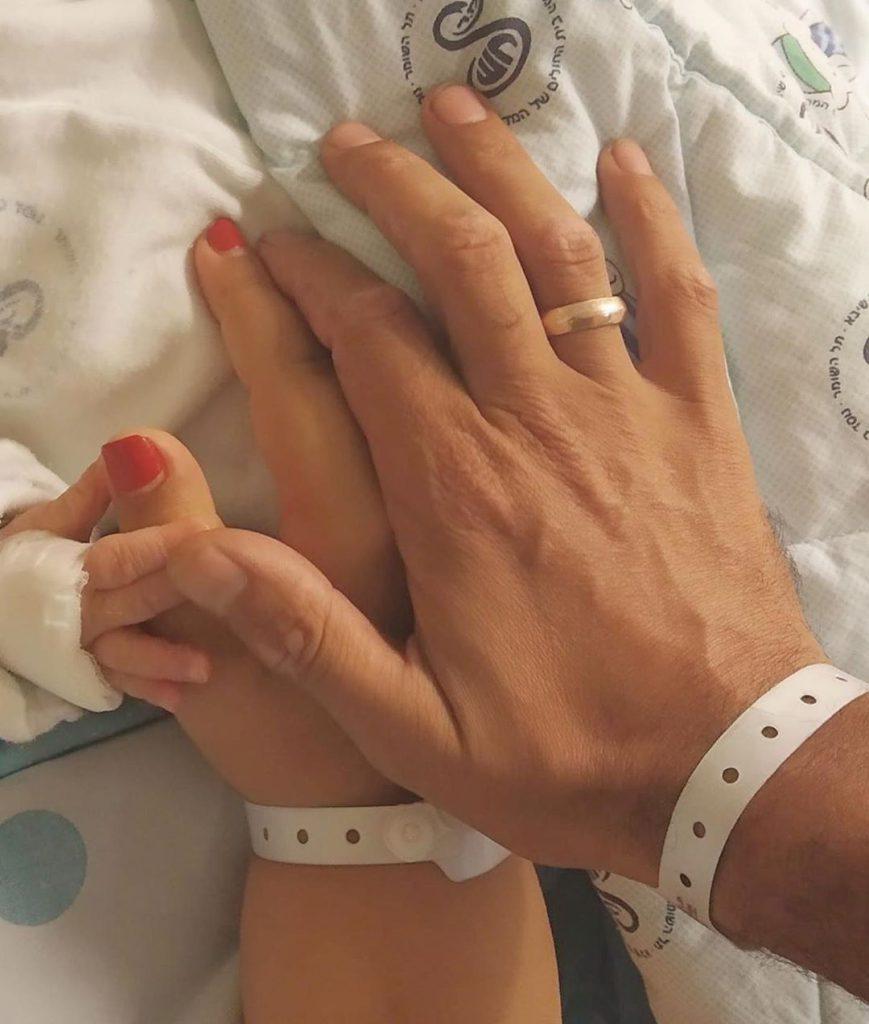 5אמירה בוזגלו ובעלה משה בן שימול אוחזים בידו הקטנה של בנם